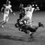 Football player tackling another player.
