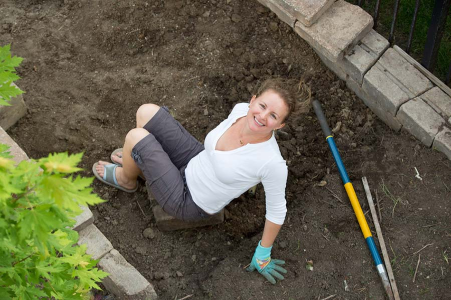 Woman in pile of dirt landscaping her property