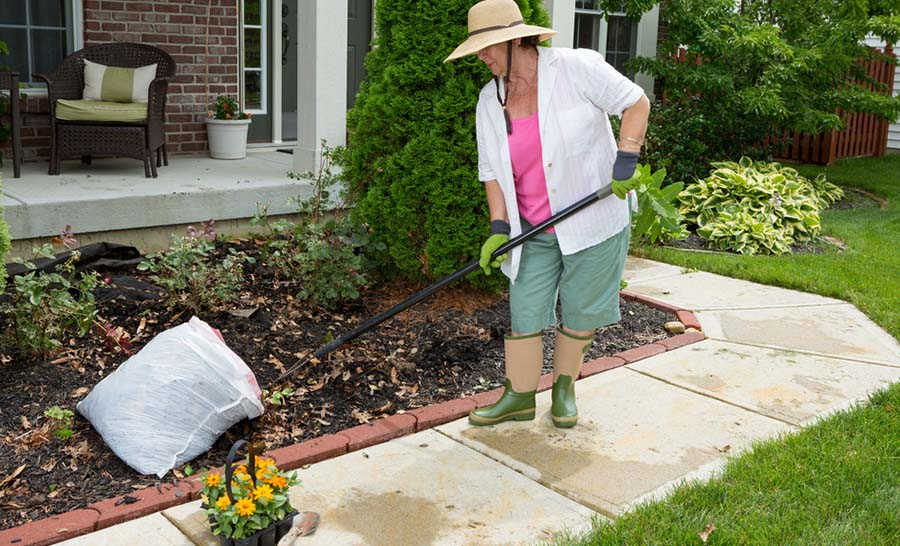 Older women adding mulch to her gardens and landscaping