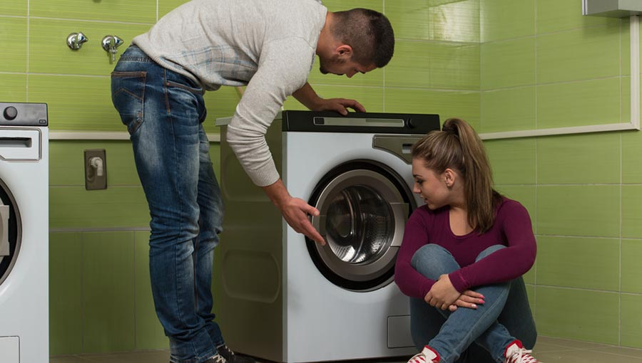 Man showing women how to use front loading washer