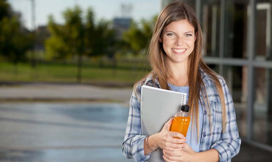 Women university student holding books and a beverage