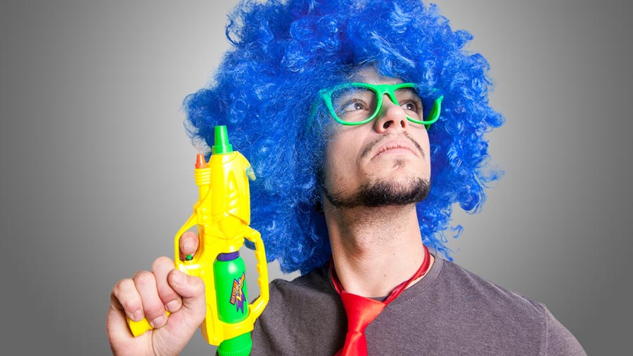 Man with blue afro, green sunglasses and a water gun