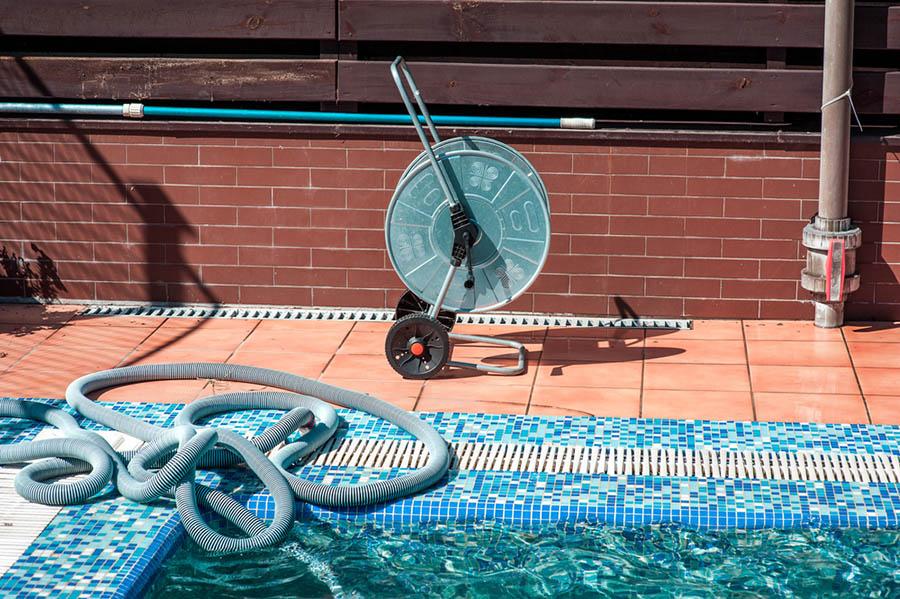 Inground pool with maintenance equipment beside it