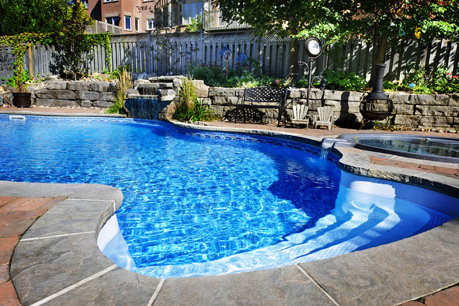 Backyard in ground pool with hot tub and surrounding landscaping