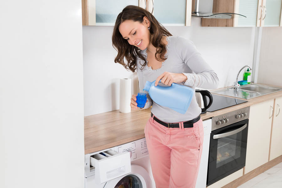 Women pouring dishsoap into her front loading washer