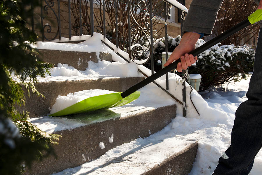 A person shovels snow from the stairs of their doorstep