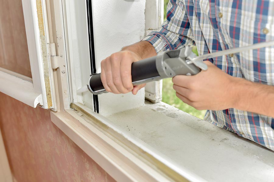 A person applying caulking to a window to prevent air leaks