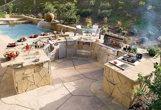 Wrap around outdoor kitchen beside a swimming pool
