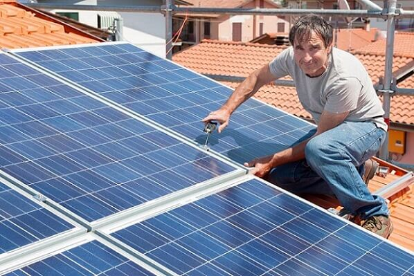 Person on a roof installing a solar panel