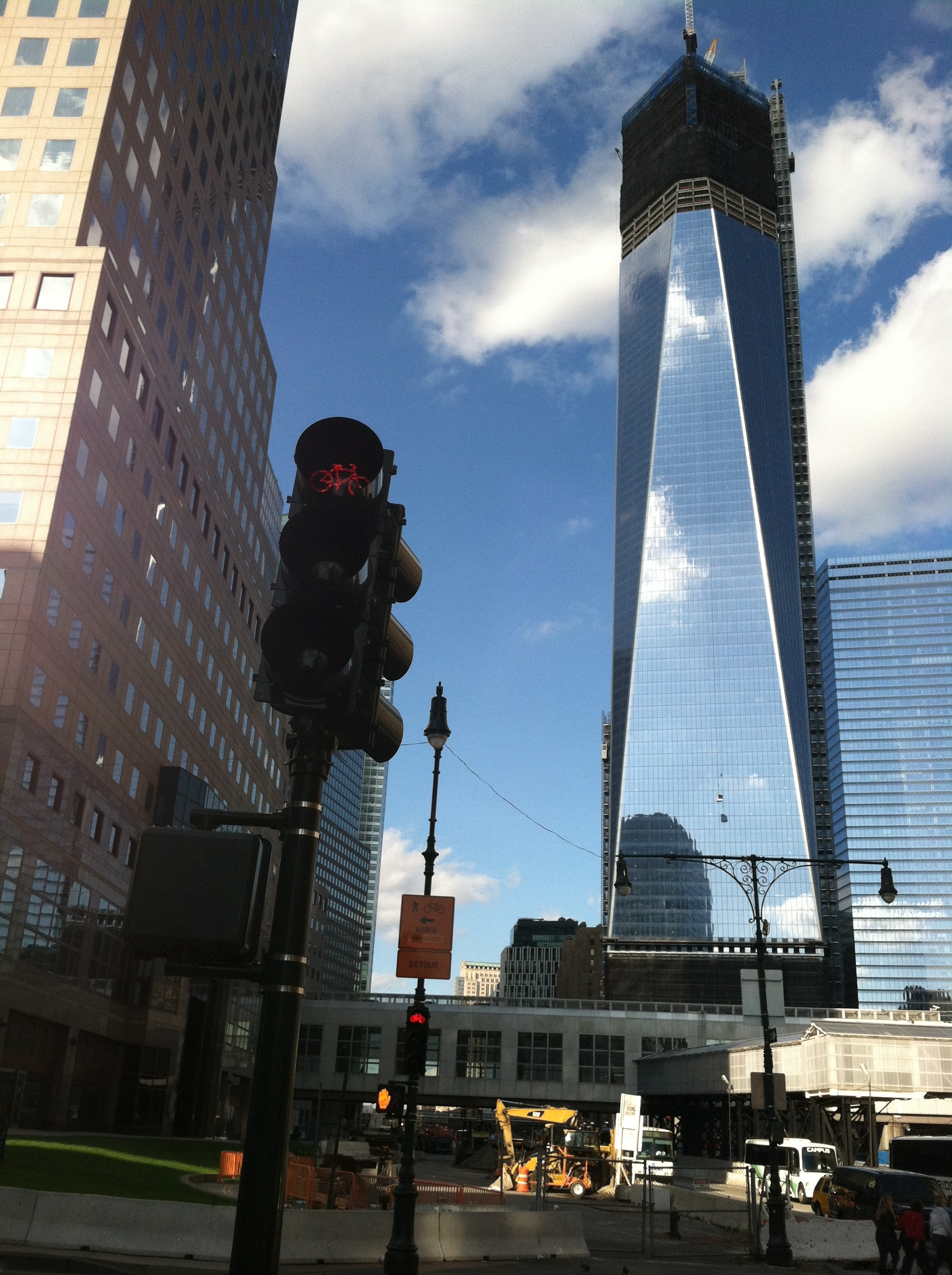A bike-specific traffic signal foregrounding the construction of the new World Trade Center Towers