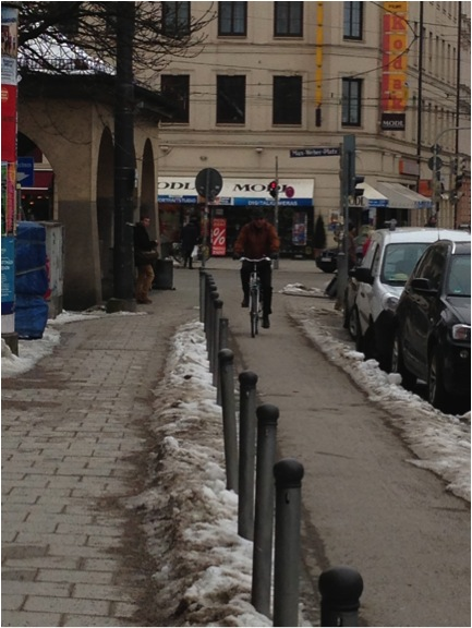 Most protected lanes in Munich are at sidewalk grade, whereas American designs usually prefer that they be located in the roadway. Intersections follow the Dutch model.**