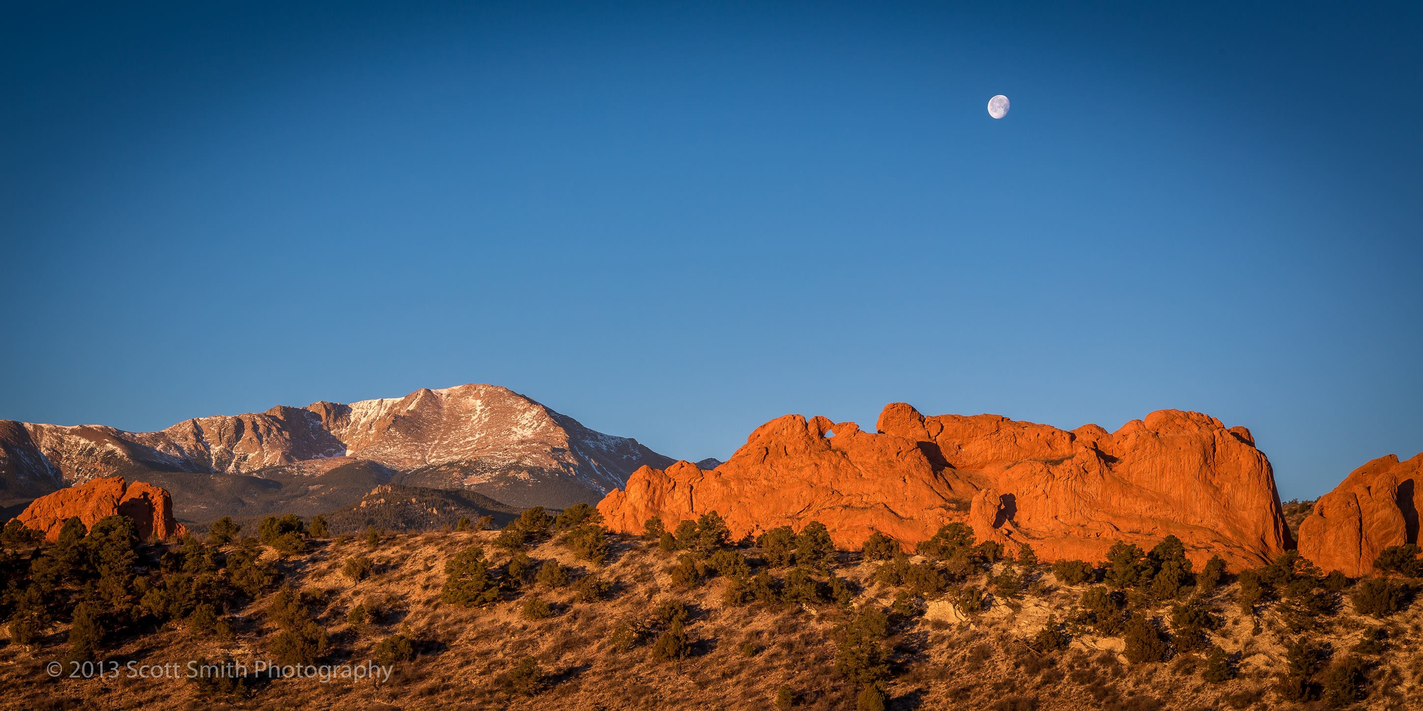Sun Rising, Moon Setting - The moon sets as the morning sun lights up the Garden of the Gods and Pike's Peak in Manitou Springs, Colorado. by D Scott Smith