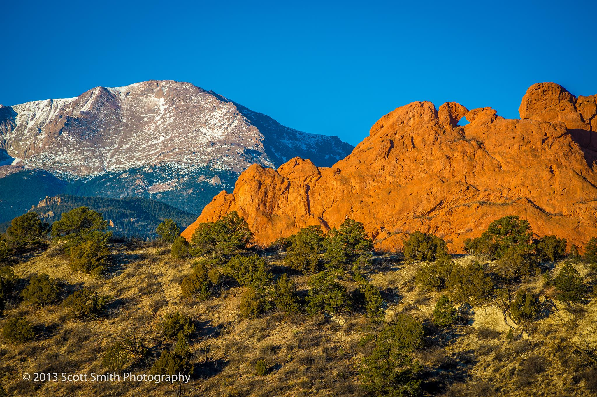 Sun rising on the Garden of the Gods - The Garden of the Gods earlier in the morning with Pike's Peak in the background. by D Scott Smith