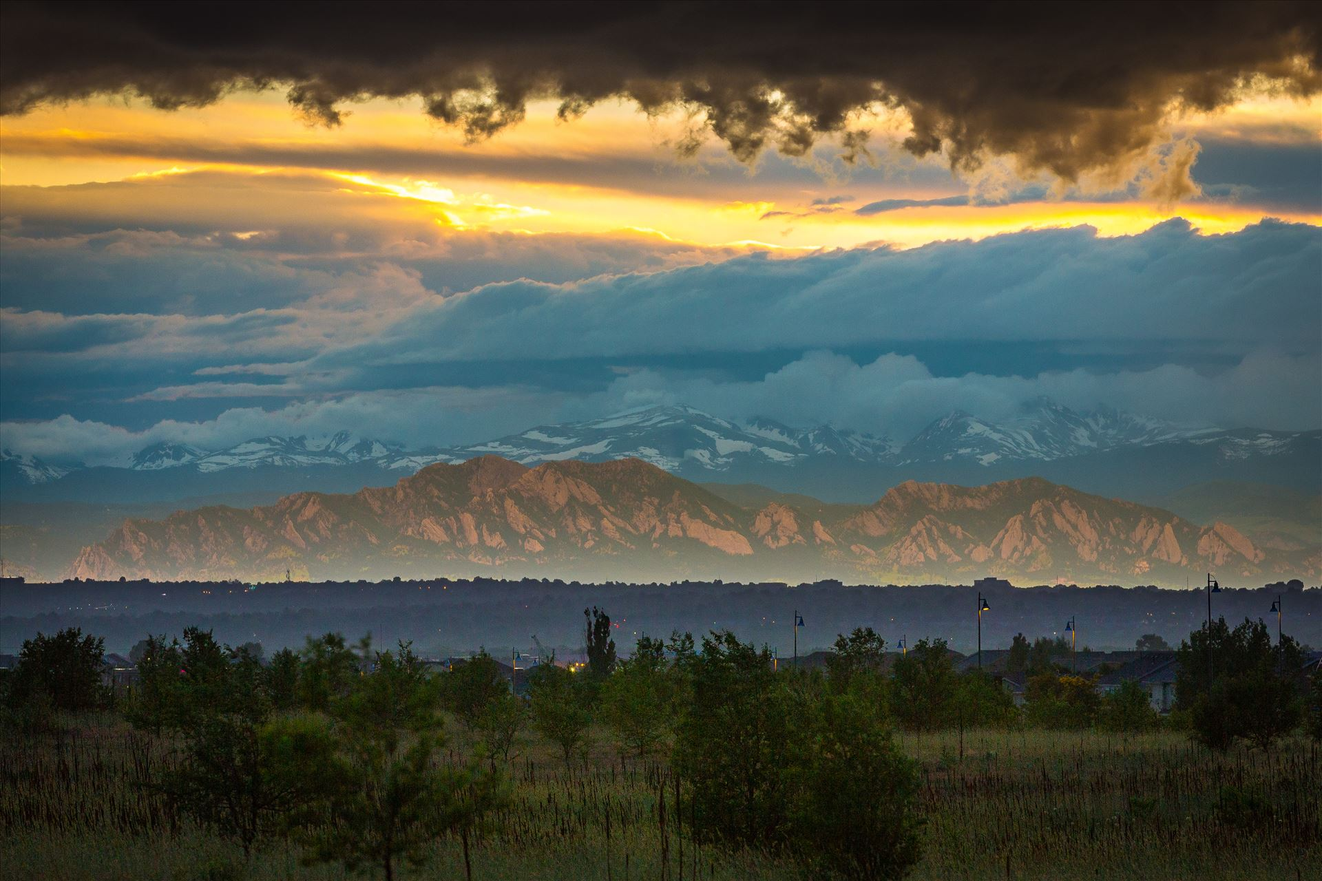 Relected Light on the Flatirons - Interesting weather phenomenon as light from the setting sun reflects on a low cloud layer onto the Flatirons in Boulder, Colorado. Taken from Commerce City, Colorado. by D Scott Smith