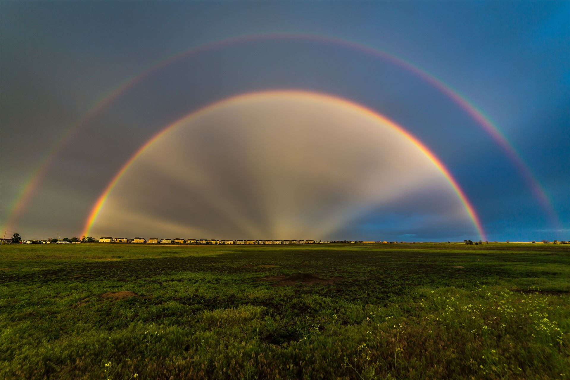 Double Rainbow with Anti-Crepuscular Rays - After a hard rain and a bit of hail, anti-crepuscular rays appear to cast from the center of a double rainbow, near Reunion, Colorado. by D Scott Smith