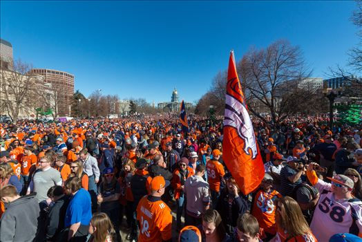 Fans of the Denver Broncos completely fill Civic Park in Denver Colorado. The state capitol building is visible in the center of the frame.