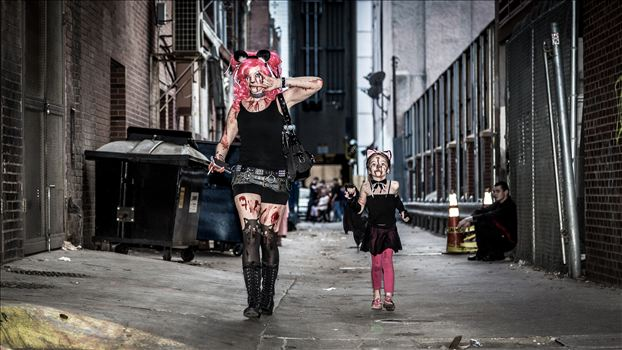 An adorable mother and daughter walking through an alley during Denver's 2015 Zombie Crawl.