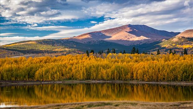 A small lake between South Park and Fairplay, Colorado reflects the fall aspens as the sun sets on a beautiful weekend.