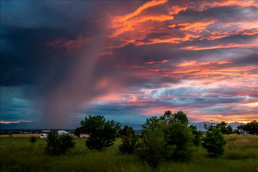 A storm rolls in just as the sun sets, highlighting the clouds with beautiful colors.