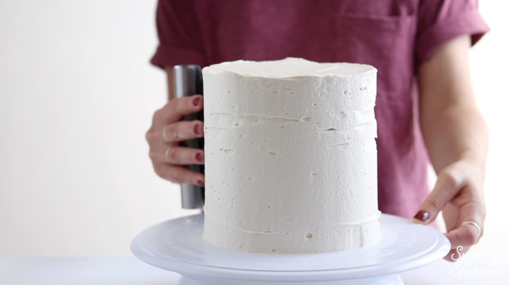 using a bench scraper to frost a cake