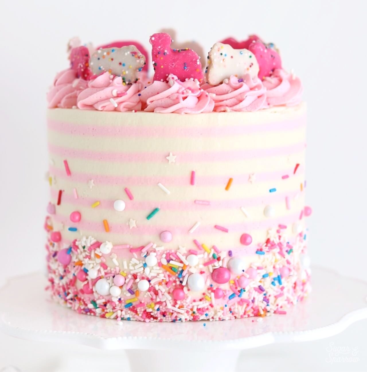 pink and white striped circus cake with sprinkles