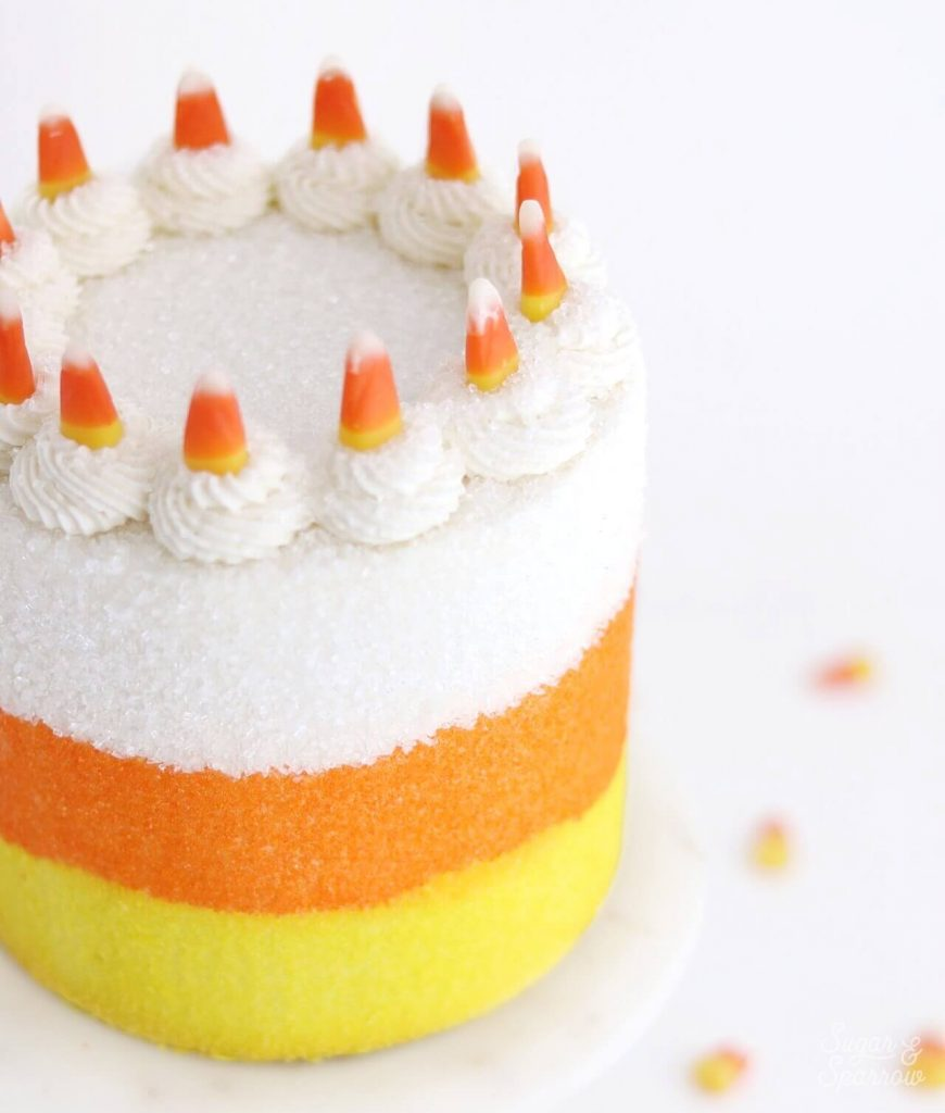 cake topped with candy corn by sugar and sparrow