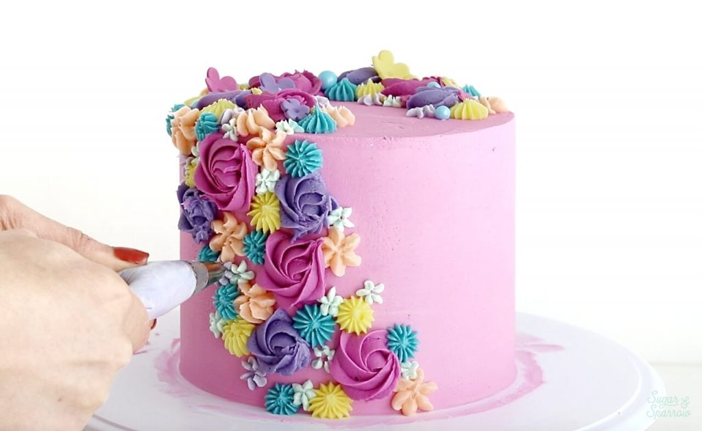 piping buttercream flowers onto cake