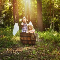 31754839 - a little boy and girl are pretending to fish in a wooden barrel boat in the nature woods with a real fish being caught by the children for an imagination or creativity concept.