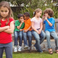 44850718 - upset child standing away from group sitting on a bench