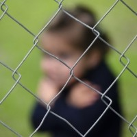 45739873 - missing kidnapped, abused, hostage, victim girl alone in emotional stress and pain, afraid, restricted, trapped, call for help, struggle, terrified, threaten, behind a fence locked in a cage cell