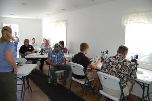 participant sit at microscopes learning to identify insects.