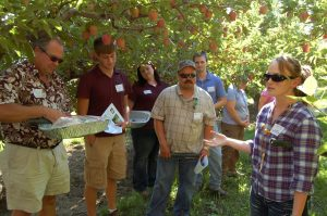 industry fieldmen standing in an apple orchard listening to student instructor.