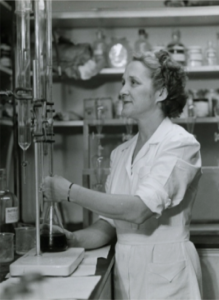 1950s era female chemist using titration equipment.