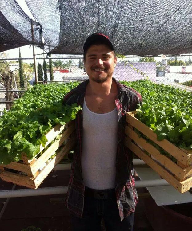 Cesar Reyes Corral holding plants