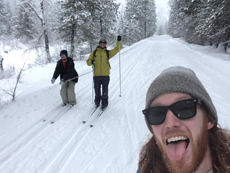 two people cross country skiing posed behind a bearded man taking the picture