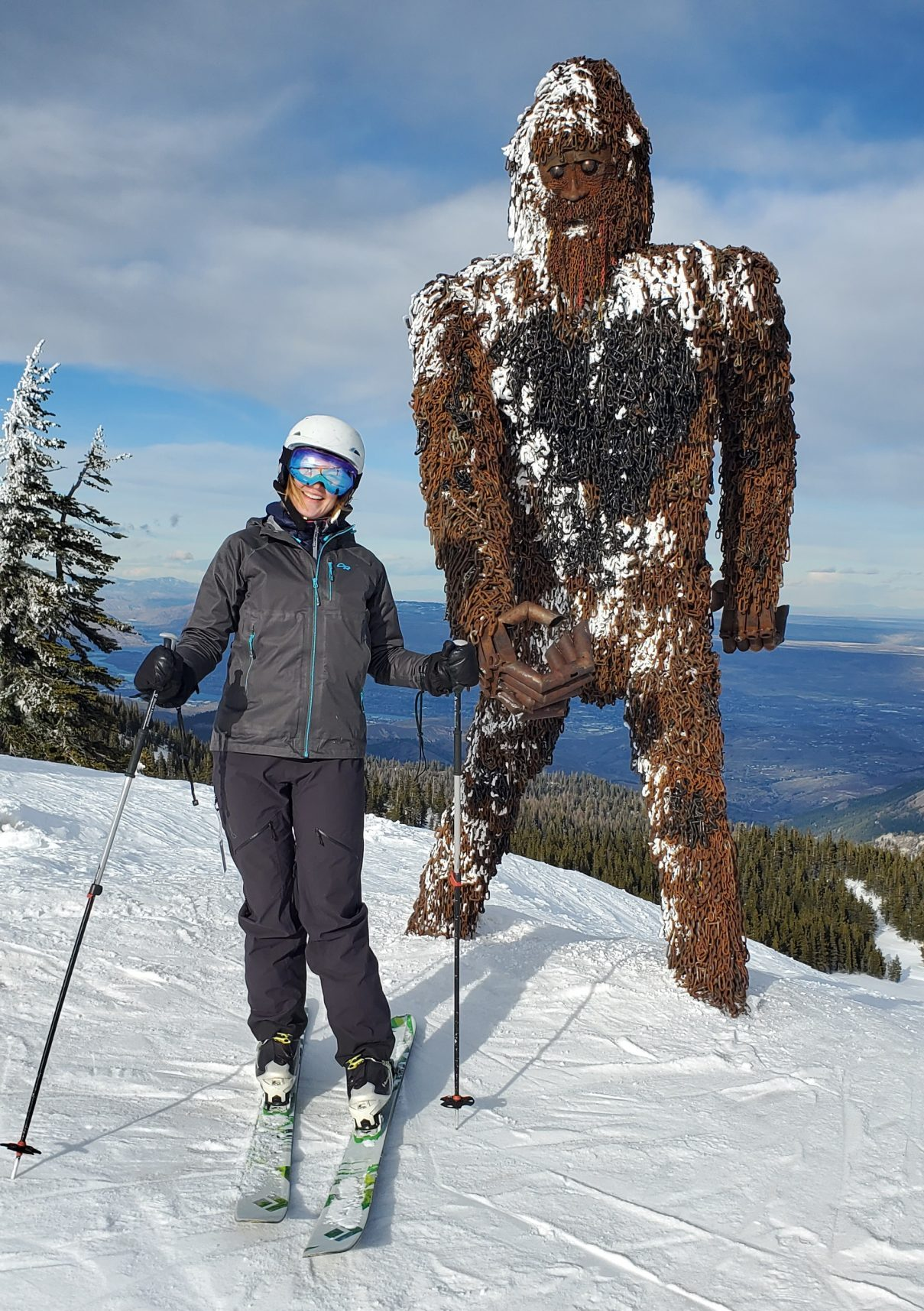 woman on skis standing in front of a very tall yeti sculpture at the top of mission ridge ski area