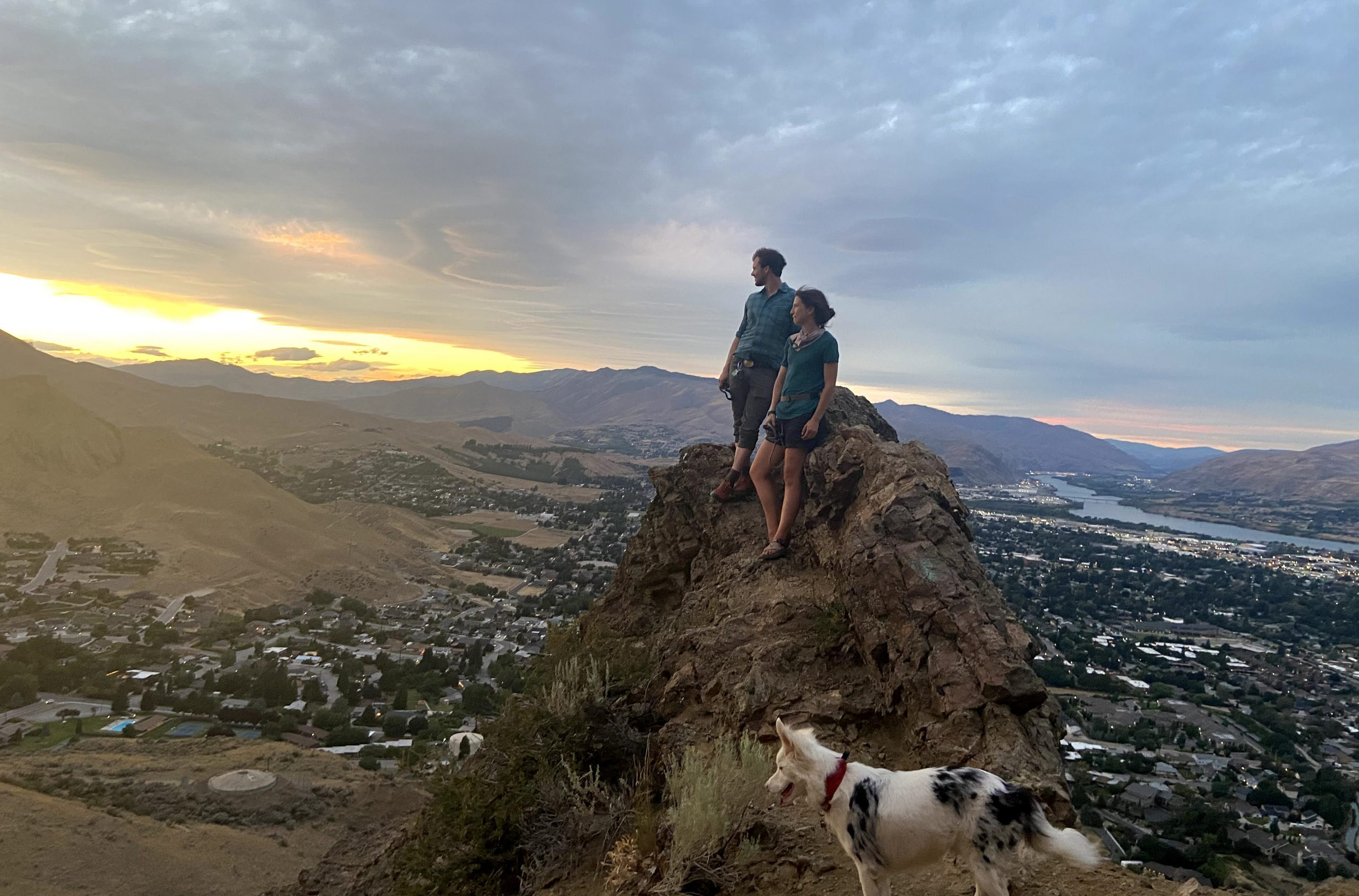 two people standing on a rocky spire at sunset with the town of wenatchee far below. a white dog with black spots is in the foreground