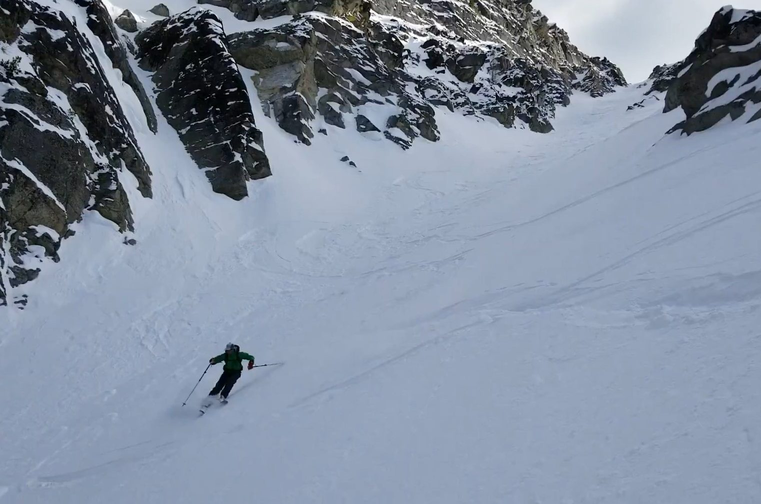 man skiing down the face of a backcountry mountain with craggy black rocks in the background