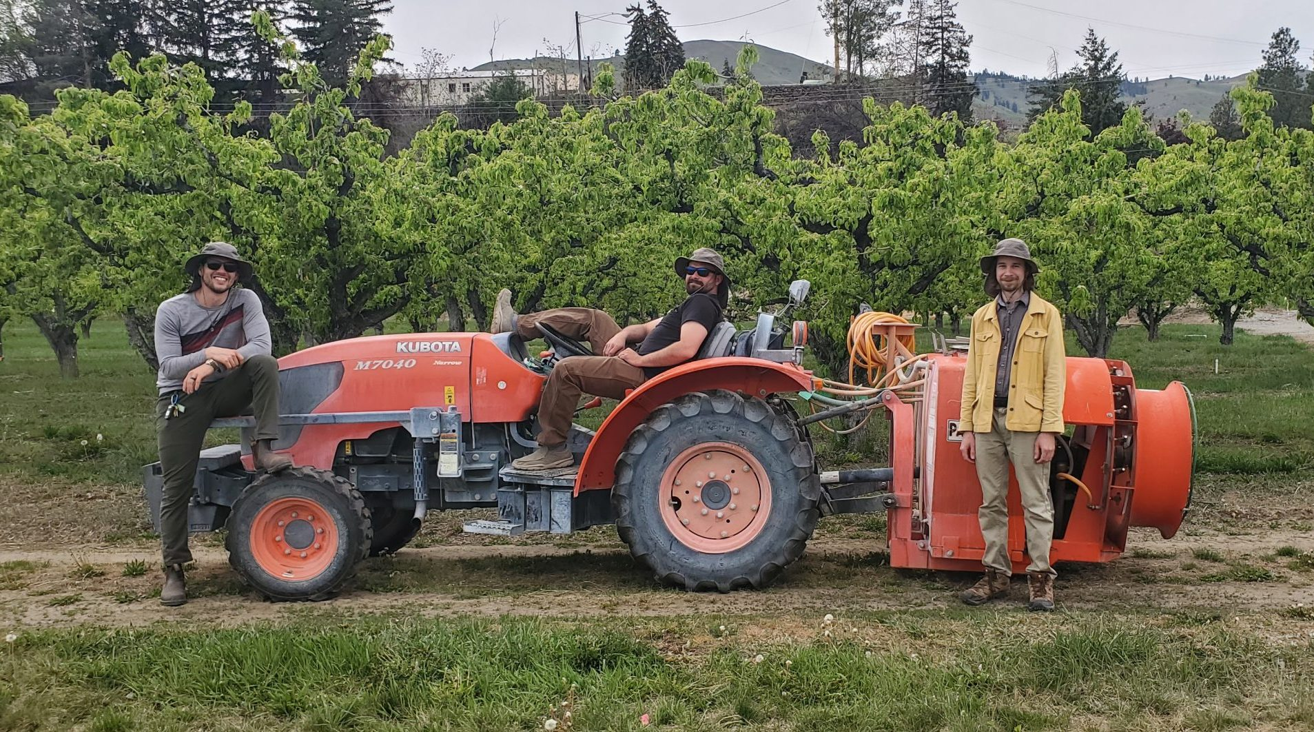 orange tractor with sprayer attachment. three people are posed, one in front, one lounging on the seat and one in front of the sprayer attachment