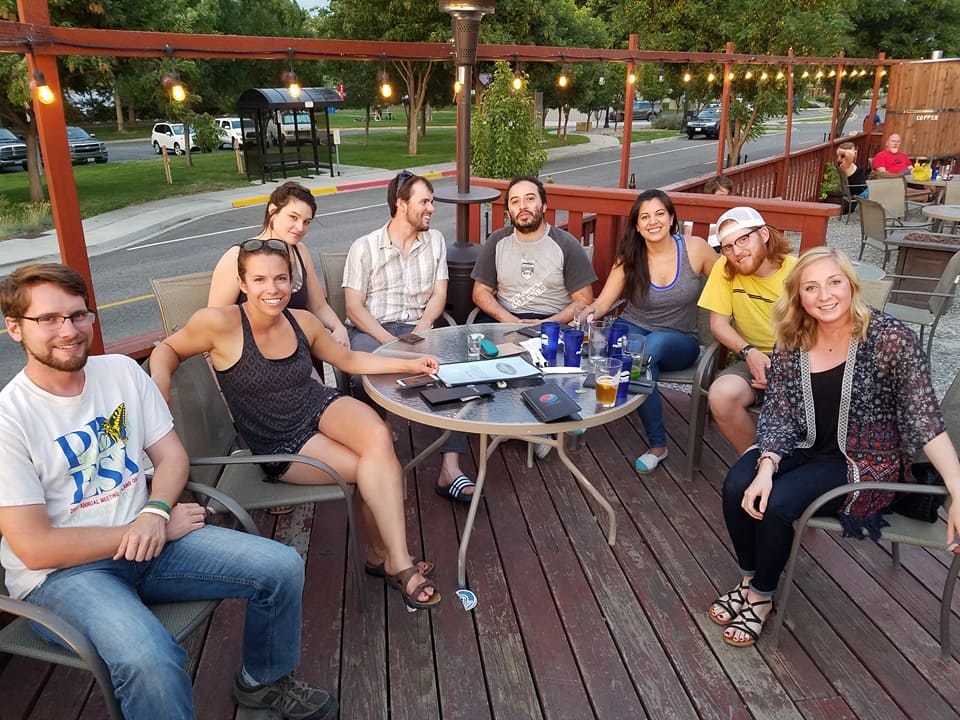 8 smiling people sitting around a table on a deck
