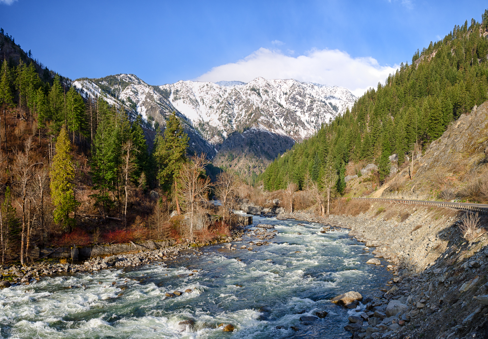 river between two wooded hills with snowy mountains in the background
