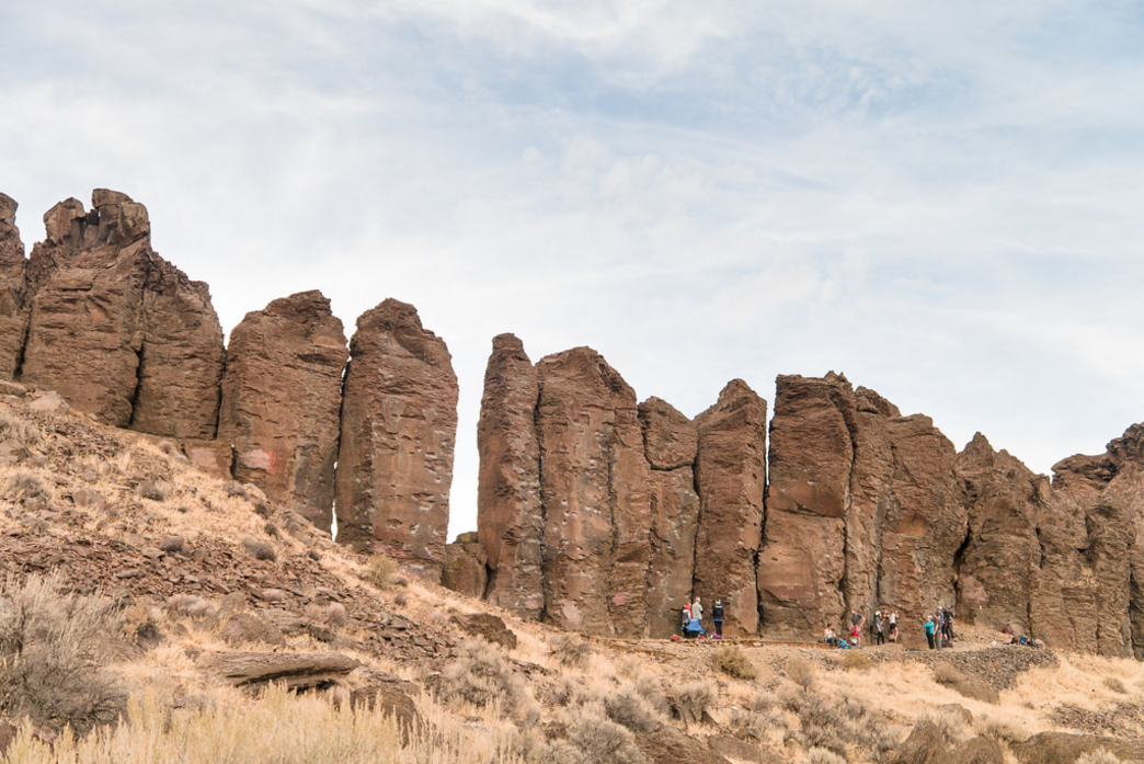 landscape view of climbers looking very small in front of columnar basalt formations