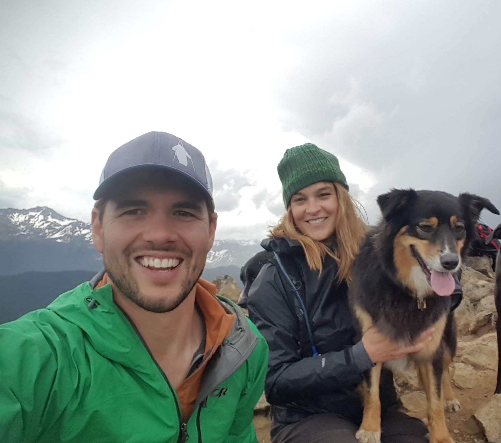 a man, a woman and a really cute dog with snow-covered mountains in the background