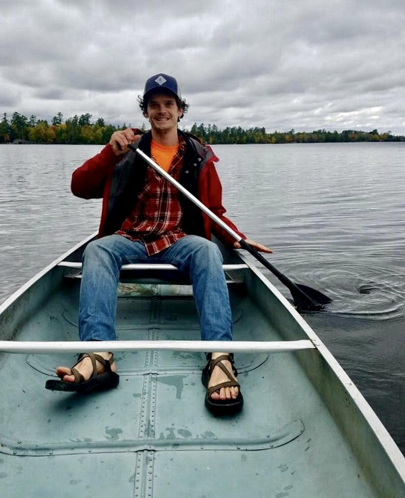 man in a red sweatshirt and baseball cap sitting in an aluminum canoe paddling on a lake