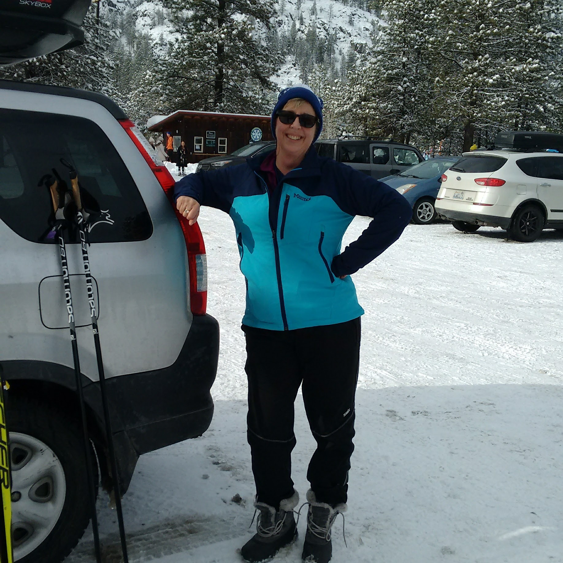 a smiling woman wearing a blue and teal jacket and matching hat and sunglasses is leaning on a silver car in a snowy parking lot