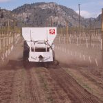 compost spreader drives between rows of baby trees