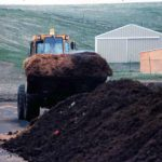 front end loader carrying raw materials to form windrow