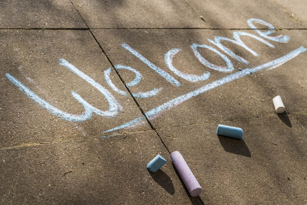 Welcome written on the sidewalk with chalk.