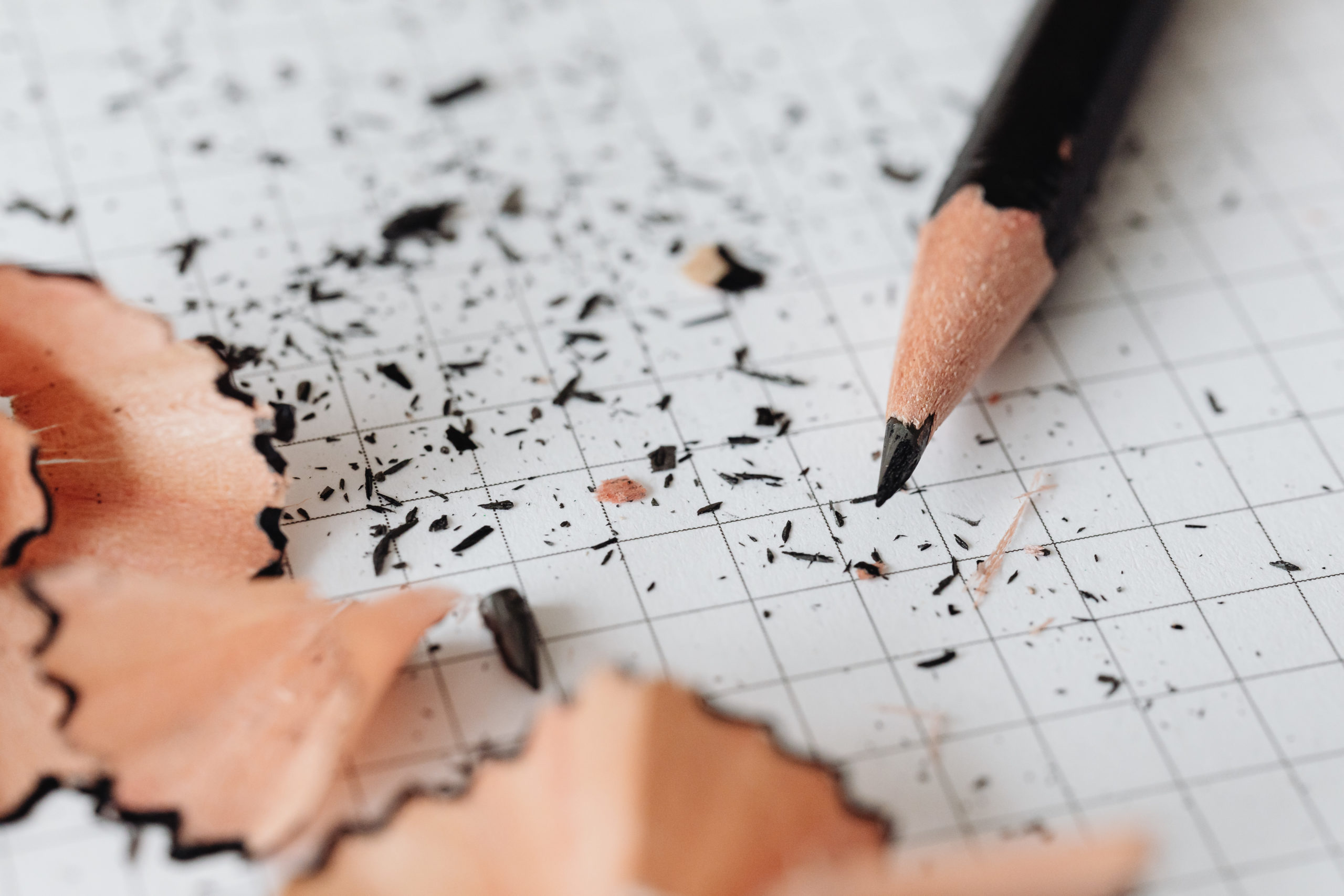 Picture of a pencil and sharpener shavings on graph paper.