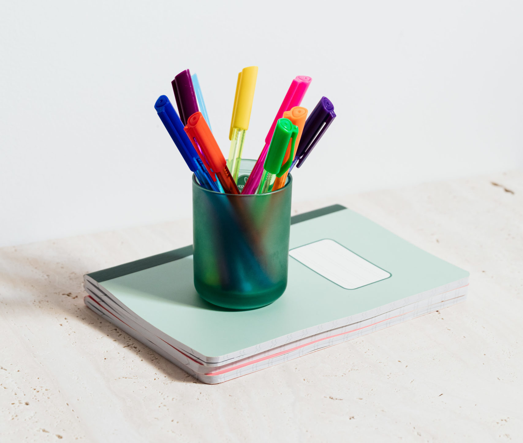 Picture of pens in a cup on a notebook.